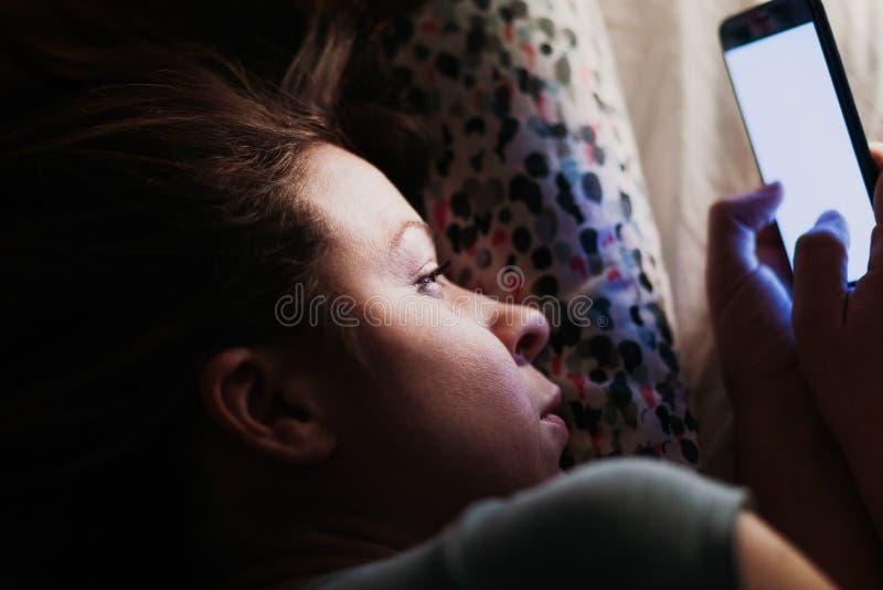 Jeune femme à l'aide du smartphone dans le lit photographie stock libre de droits