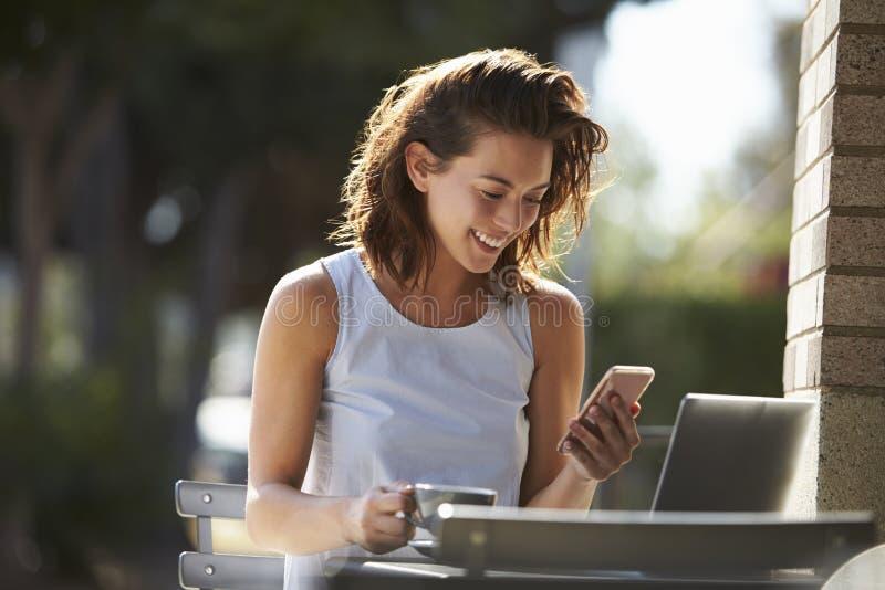 Jeune femme à l'aide du smartphone et de l'ordinateur portable en dehors d'un café images libres de droits