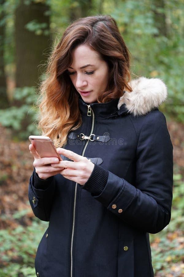 Jeune femme à l'aide du smartphone mobile dehors image libre de droits