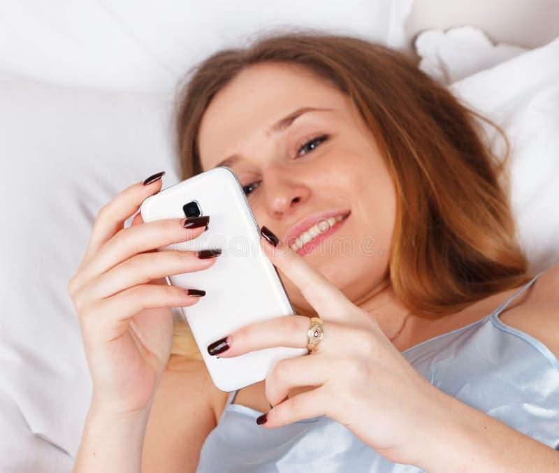 Jeune femme à l'aide du smartphone sur le lit photos libres de droits