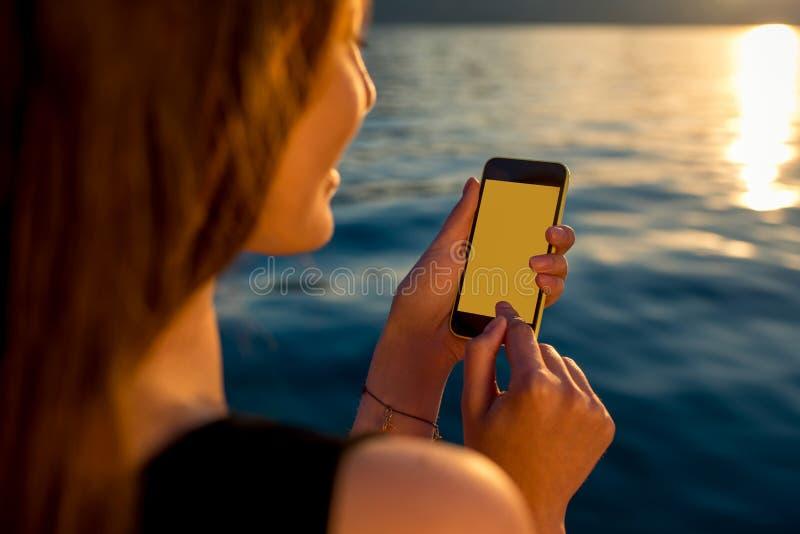 Jeune femme à l'aide du téléphone au lever de soleil images stock