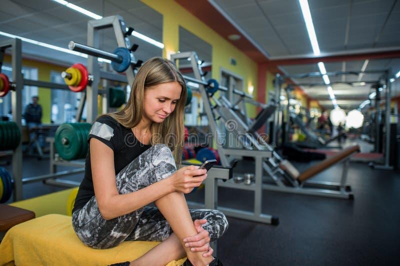 Jeune femme à l'aide du téléphone dans le gymnase image stock
