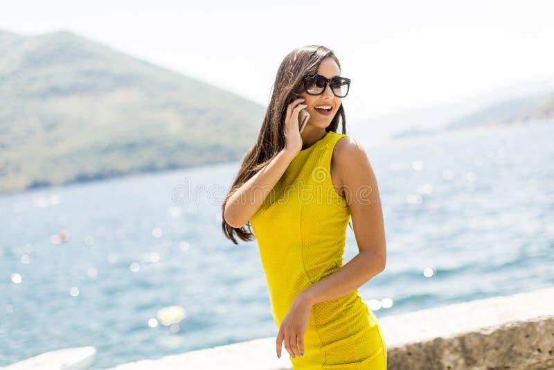 Jeune femme à l'aide du téléphone mobile par la mer image libre de droits