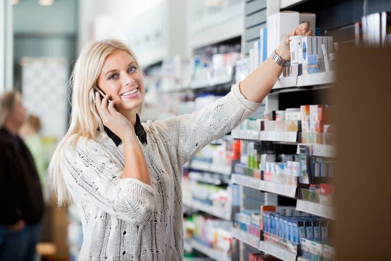 Jeune femme à l'aide du téléphone portable dans la pharmacie image libre de droits