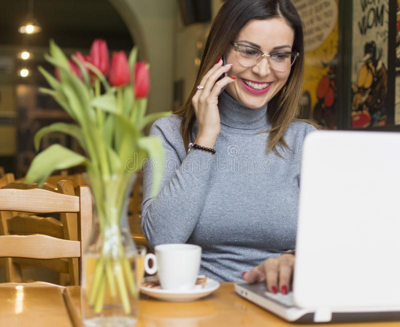 Jeune femme à l'aide du téléphone portable dans le café image libre de droits