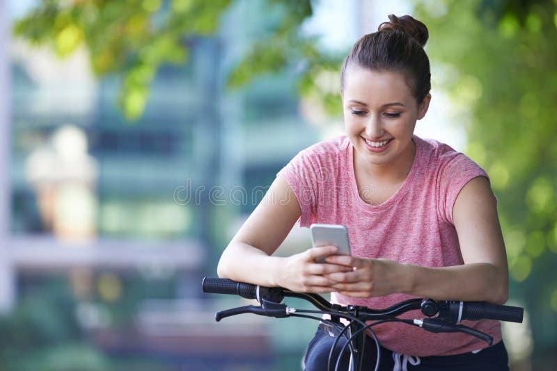 Jeune femme à l'aide du téléphone portable tandis que sur le tour de cycle photos libres de droits