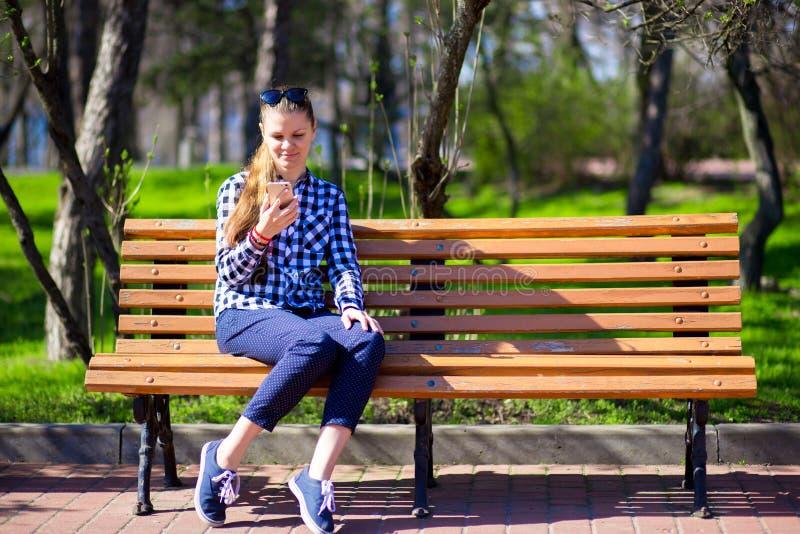 Jeune femme à l'aide du téléphone portable tout en se reposant dans le parc image libre de droits