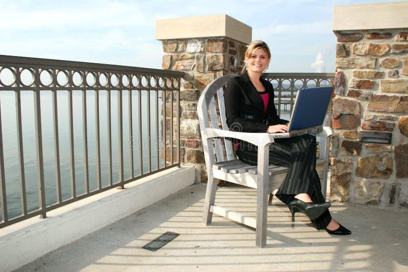 Jeune femme à l'extérieur au lac avec l'ordinateur portatif photographie stock
