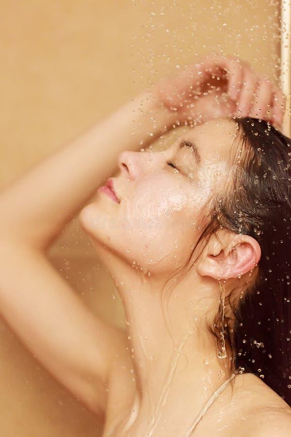 Jeune femme à la douche images stock