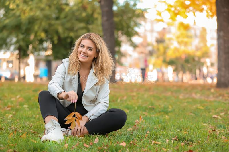 Jeune femme à la mode avec des feuilles d'automne se reposant sur l'herbe verte en parc photographie stock