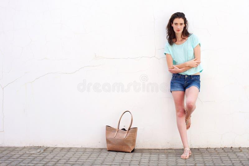 Jeune femme à la mode avec la bourse se penchant contre le mur blanc image stock