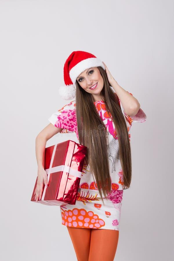Jeune femme à la mode avec le chapeau de Santa tenant le grand boîte-cadeau photos stock
