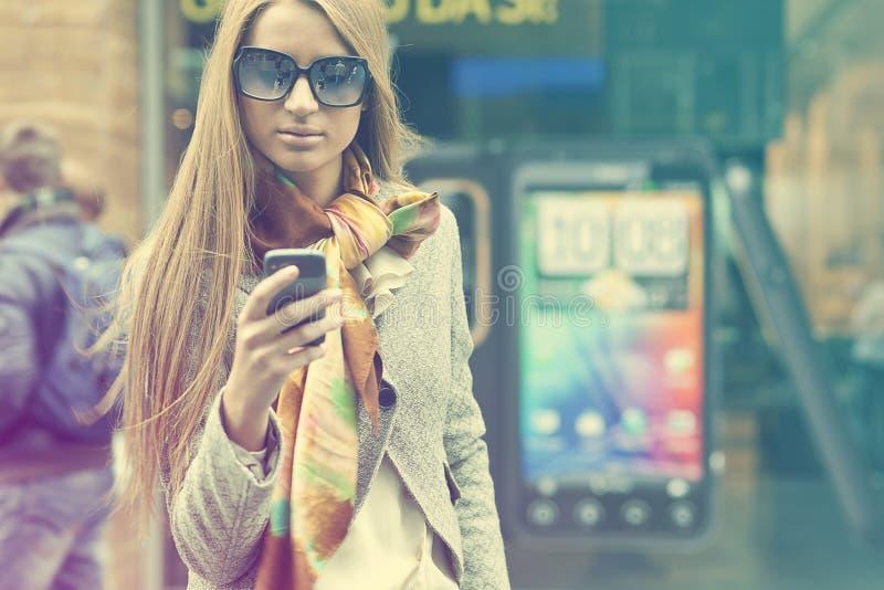 Jeune femme à la mode avec le smartphone marchant sur la rue photographie stock libre de droits