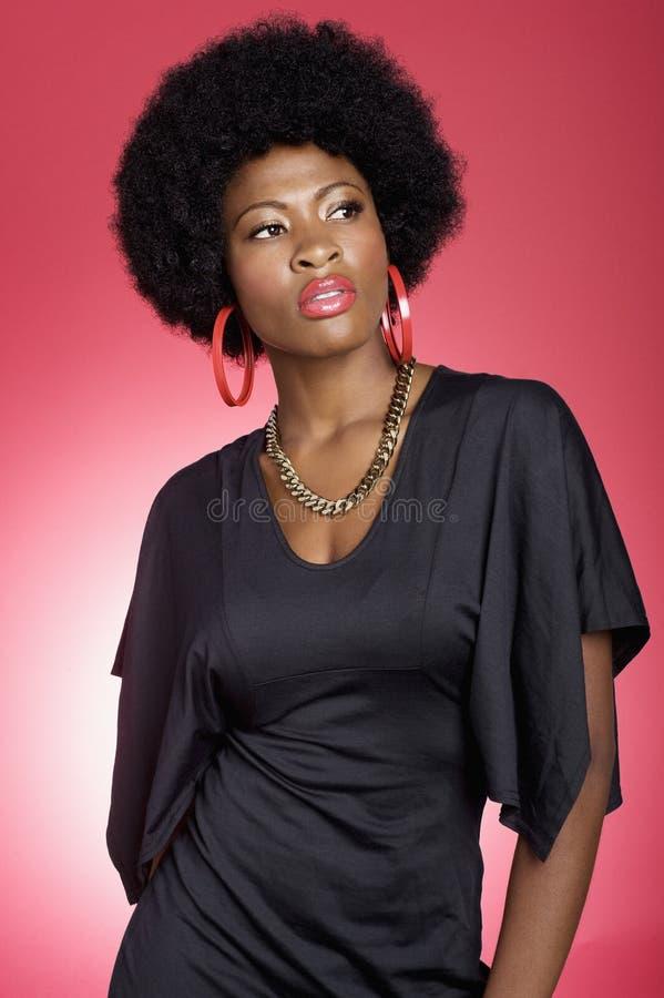 Jeune femme à la mode d'Afro-américain au-dessus de fond coloré images stock