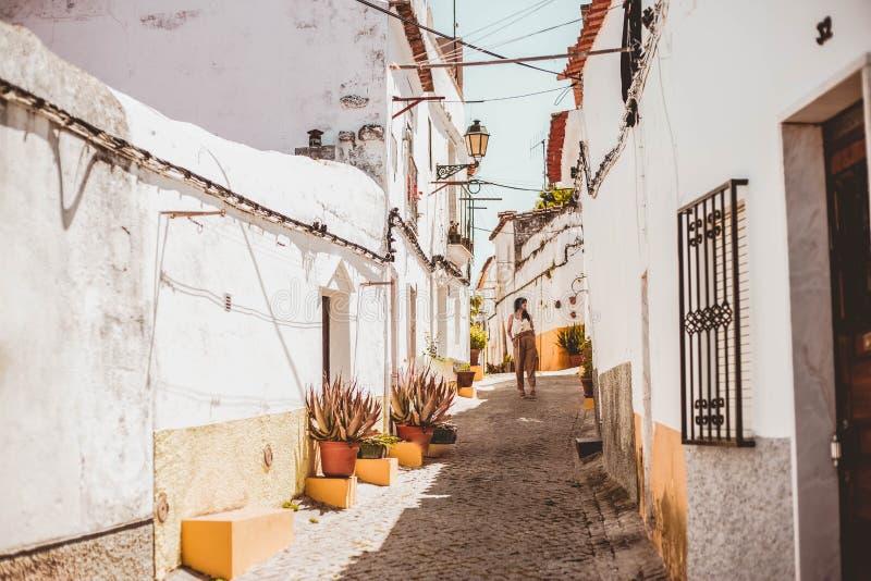 Jeune femme à la mode de brune descendant une rue une dans Elvas, Portugal images stock