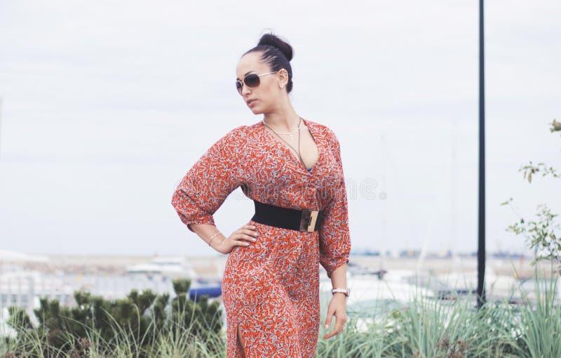 Jeune femme à la mode de brune portant la longue robe dans des lunettes de soleil posant près de la mer, pilier avec des yachts images stock