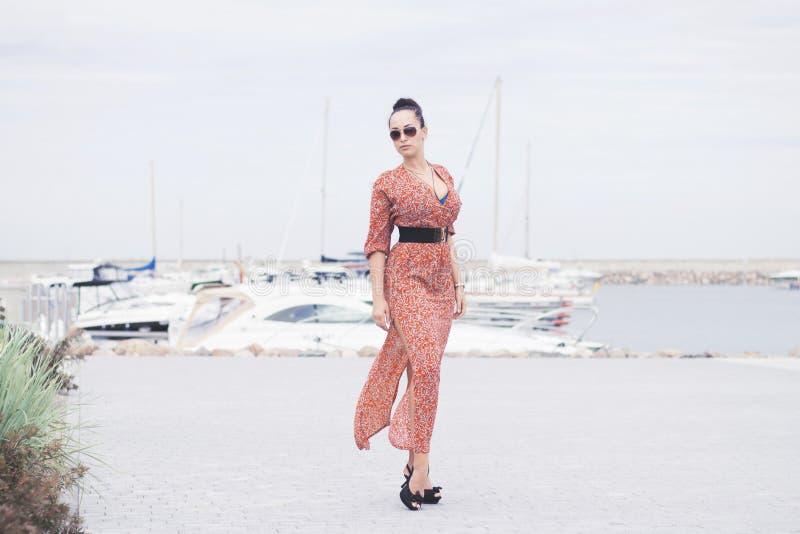 Jeune femme à la mode de brune portant la longue robe dans des lunettes de soleil posant près de la mer, pilier avec des yachts image libre de droits