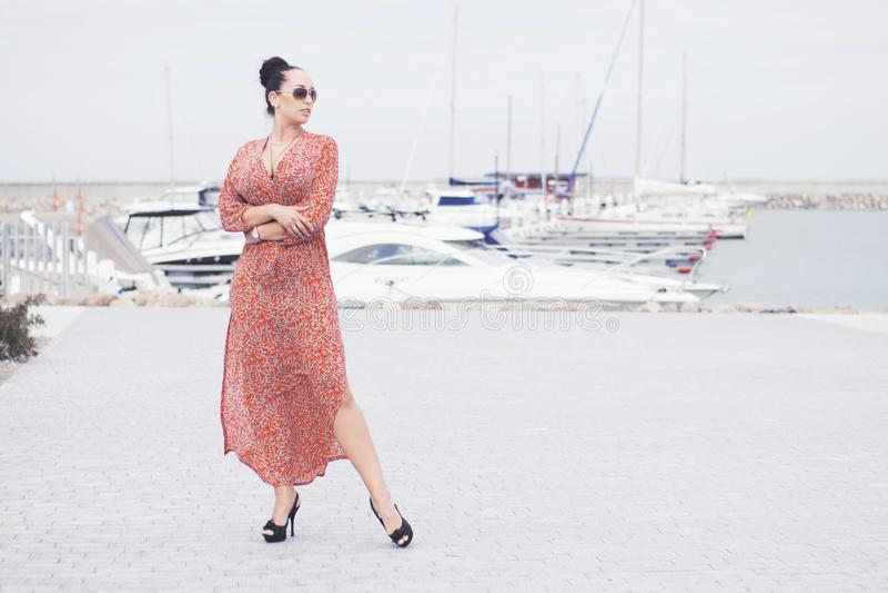 Jeune femme à la mode de brune portant la longue robe dans des lunettes de soleil posant près de la mer, pilier avec des yachts photos stock