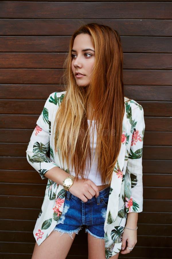 Jeune femme à la mode et élégante avec de longs cheveux posant dehors en été photo stock