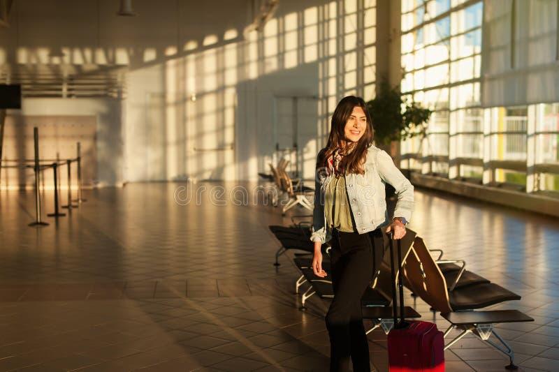 Jeune femme à la salle d'attente de terminal d'aéroport avec le sac de chariot images libres de droits
