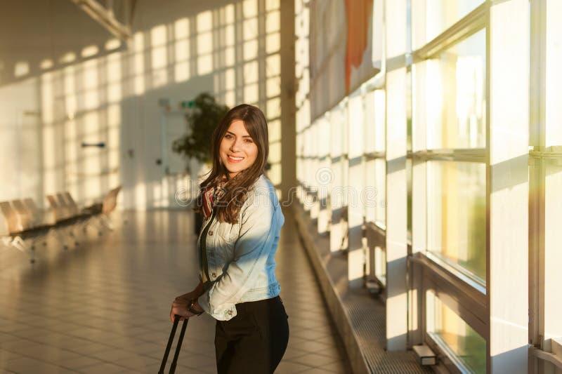 Jeune femme à la salle d'attente de terminal d'aéroport avec le sac de chariot photos libres de droits