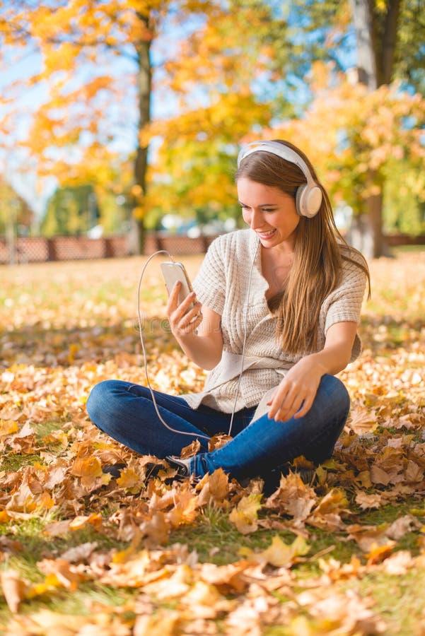 Jeune femme écoutant la musique en parc d'automne photographie stock libre de droits