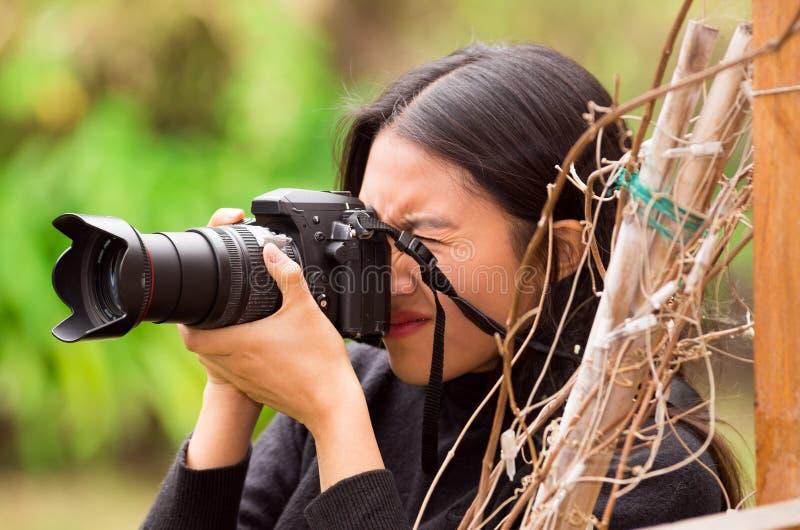 Jeune femme égrappant et prenant des photos avec son appareil-photo, à l'extérieur image libre de droits