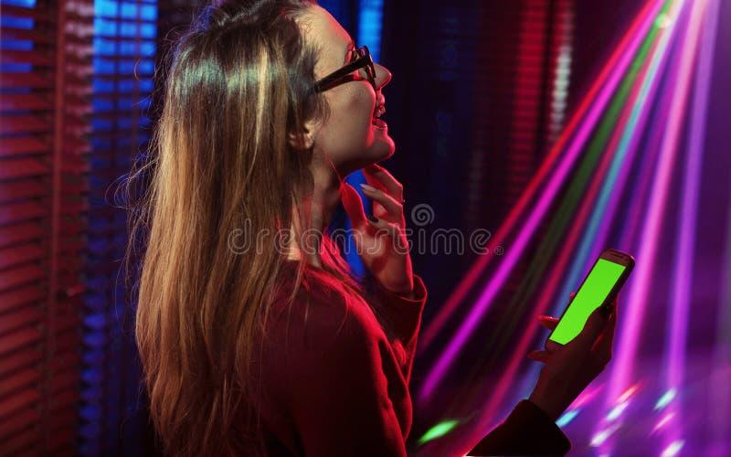 Jeune femme élégante à l'aide du smartphone à la disco photos libres de droits
