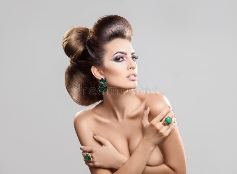 Jeune femme élégante avec la coiffure créative regardant loin dans le goujon images libres de droits