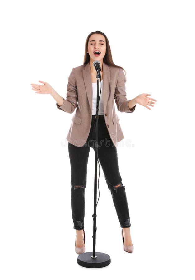 Jeune femme élégante chantant dans le microphone sur le blanc photographie stock