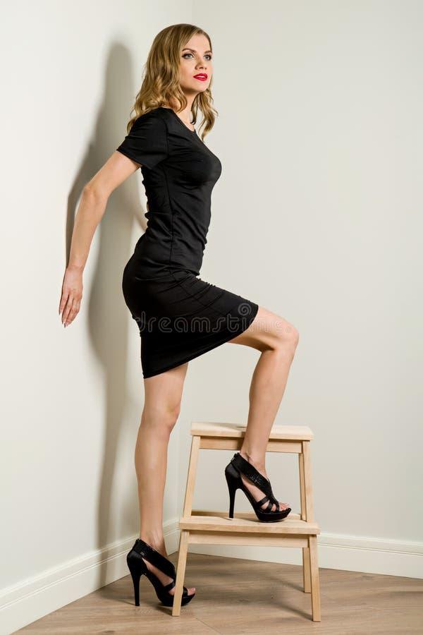 Jeune femme élégante d'affaires blonde dans la robe noire, poses près des escaliers d'un tabouret image libre de droits