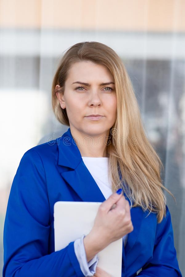 Jeune femme élégante d'affaires dans la veste bleue tenant le comprimé photographie stock