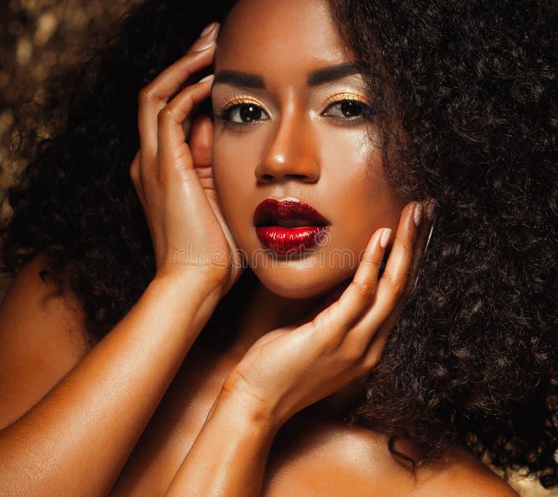 Jeune femme élégante d'afro-américain avec les cheveux Afro Maquillage de charme Fond d'or photos stock