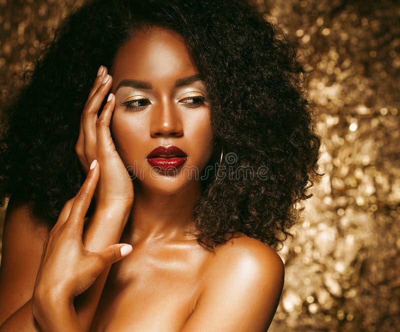 Jeune femme élégante d'afro-américain avec les cheveux Afro Maquillage de charme Fond d'or photographie stock