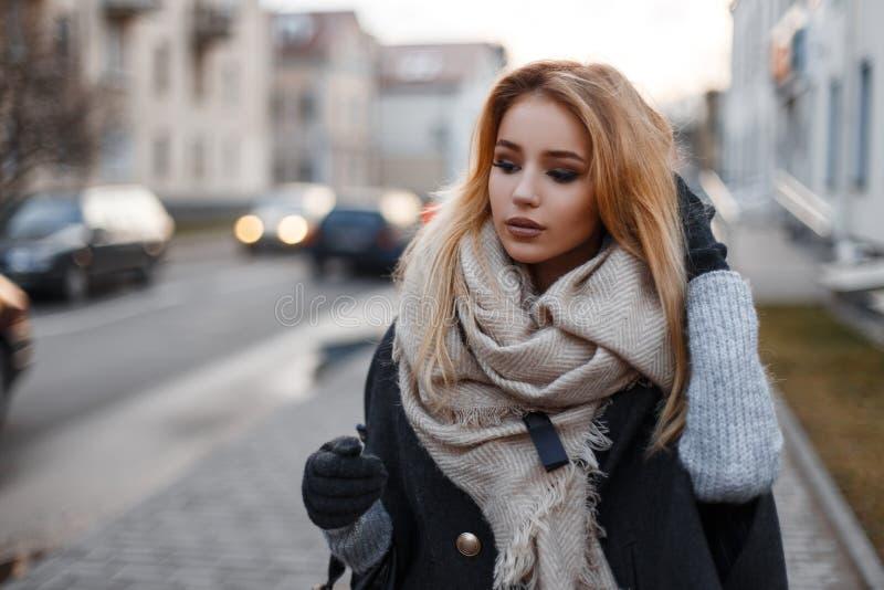 Jeune femme élégante élégante dans des vêtements à la mode d'automne descendant la rue sur le contexte des bâtiments modernes photos stock