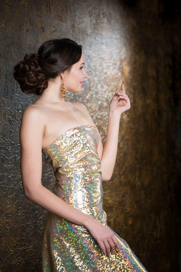 Jeune femme élégante dans la robe d'or de soirée photo libre de droits