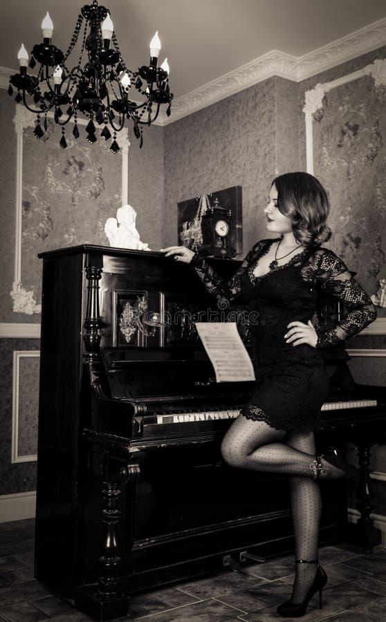Jeune femme élégante dans la robe noire posant près du piano photographie stock libre de droits