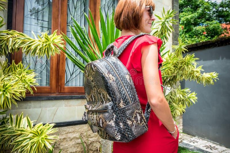 Jeune femme élégante dans la robe rouge avec le sac à dos en cuir à python de peau de serpent dans le jardin asiatique Île tropic photo libre de droits