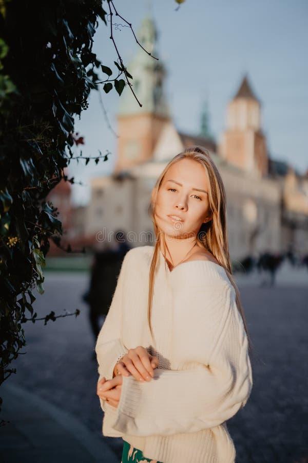 Jeune femme élégante dans une rue de ville sur la lumière du soleil photographie stock libre de droits