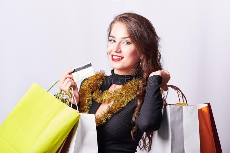 Jeune femme élégante de brune tenant les sacs à provisions et la carte de crédit colorés image libre de droits