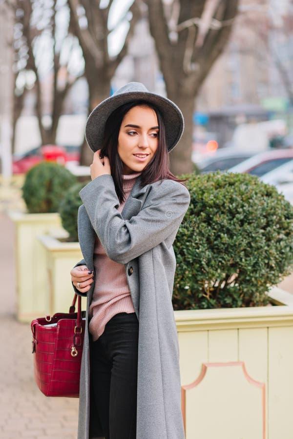 Jeune femme élégante de charme dans le long manteau gris, chapeau marchant en parc de centre de la ville Perspectives de luxe, sa images stock