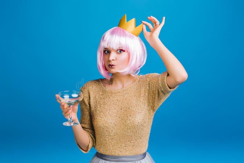 Jeune femme élégante drôle de portrait dans le chandail d'or, coupe de cheveux rose, couronne sur la tête sur le fond bleu Avoir  image stock