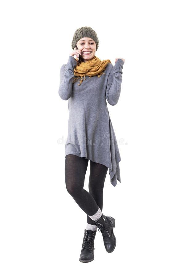 Jeune femme élégante gaie enthousiaste célébrant de bonnes nouvelles au téléphone portable photo stock