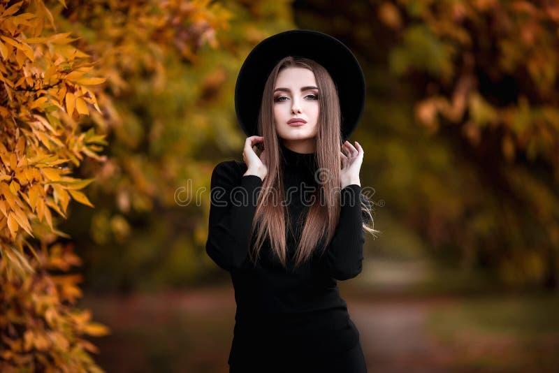Jeune femme élégante heureuse en parc le jour d'automne Belle fille gaie dans l'usage noir et chapeau dehors parmi le jaune photos libres de droits