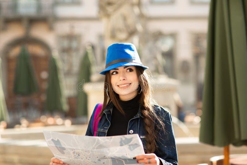Jeune femme élégante marchant sur la vieille rue de ville, le voyage avec le sac à dos et le chapeau bleu l'Ukraine, Lviv photos stock