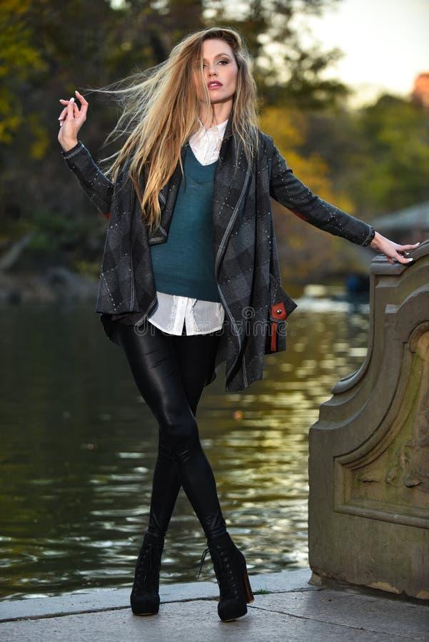 Jeune femme élégante posant contre le lac en parc images stock