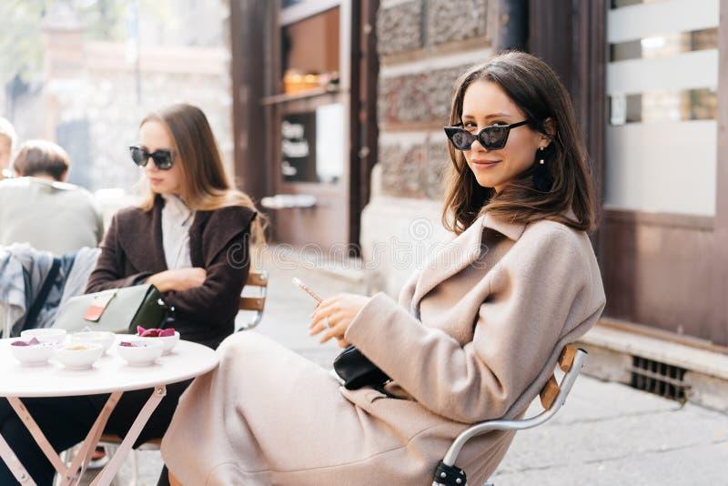 Jeune femme élégante posant en café moderne de rue images stock
