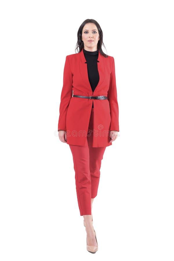 Jeune femme élégante réussie d'affaires marchant dans le costume élégant rouge photo stock