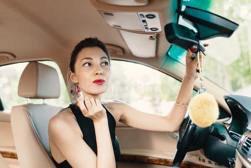 Jeune femme élégante regardant dans l'applyin de moment de miroir de vue de voiture photographie stock