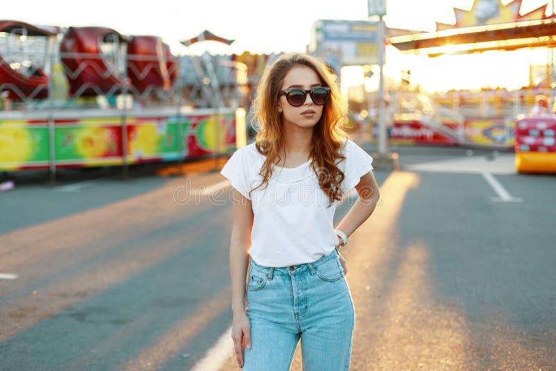 Jeune femme élégante rousse de hippie dans à la mode blanc dans des jeans de cru dans des lunettes de soleil à la mode en parc d' photographie stock
